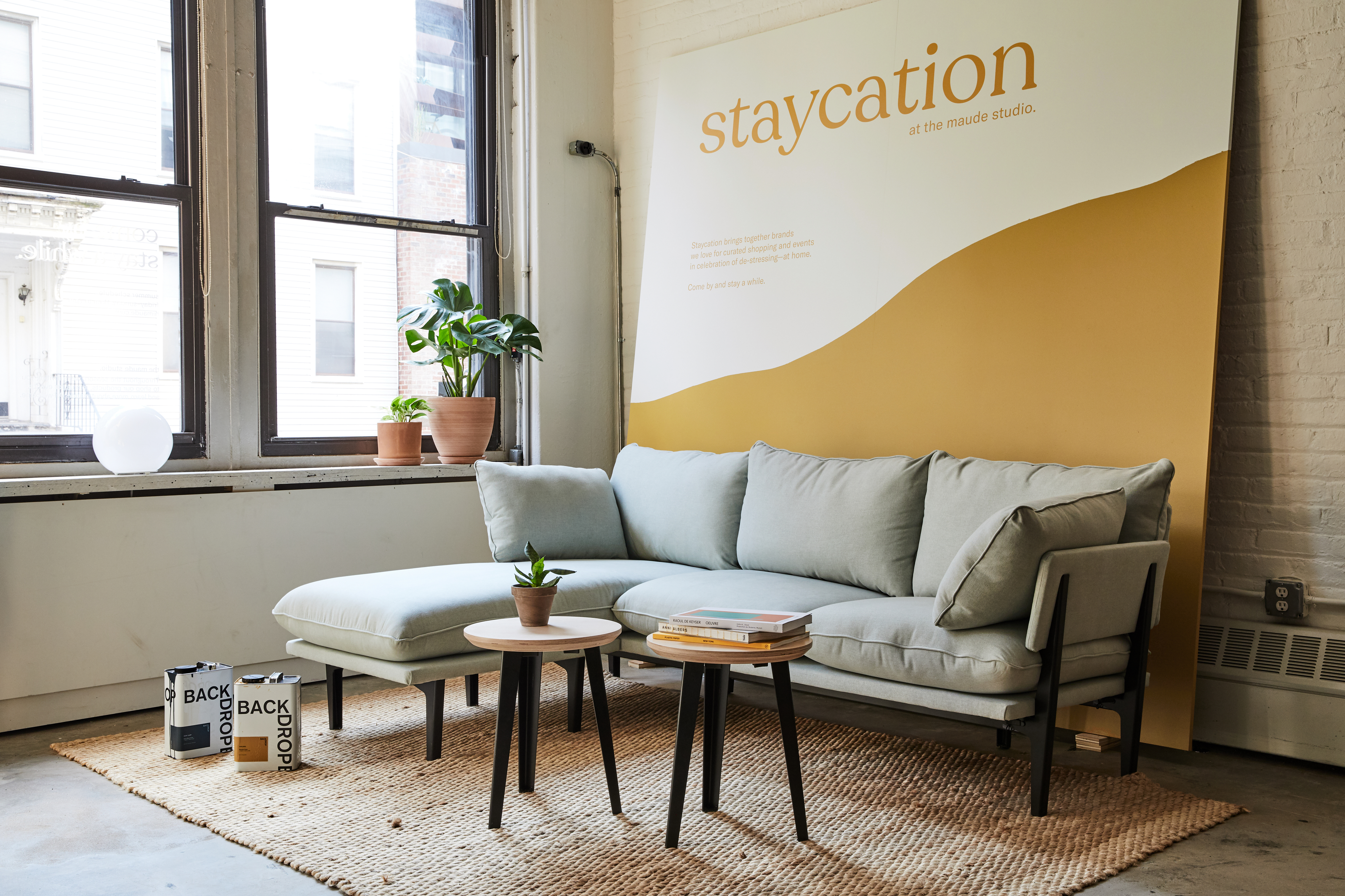maude Staycation retail popup sign and Floyd couch